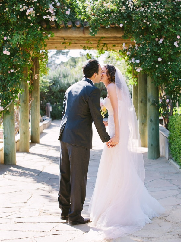 Bernardus Lodge Carmel Wedding. Bride and groom kissing under a rose covered archway.