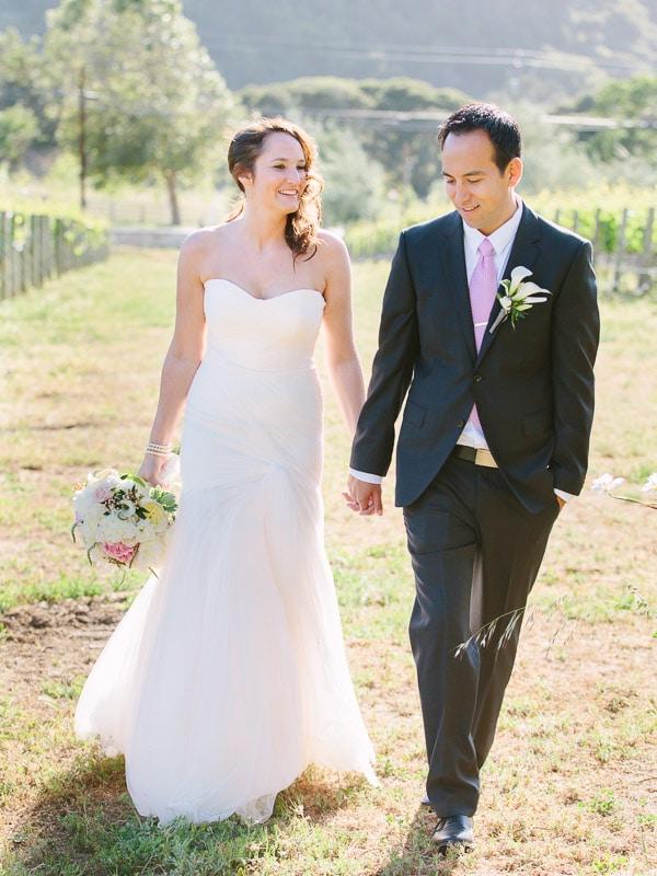 Bernardus Lodge Carmel Wedding. Bride and groom walking in vineyard.
