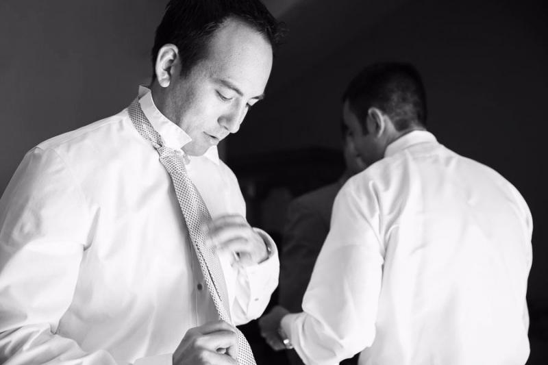 Bernardus Lodge Carmel Wedding. Black and white photo of the groom tying his necktie before his wedding ceremony.