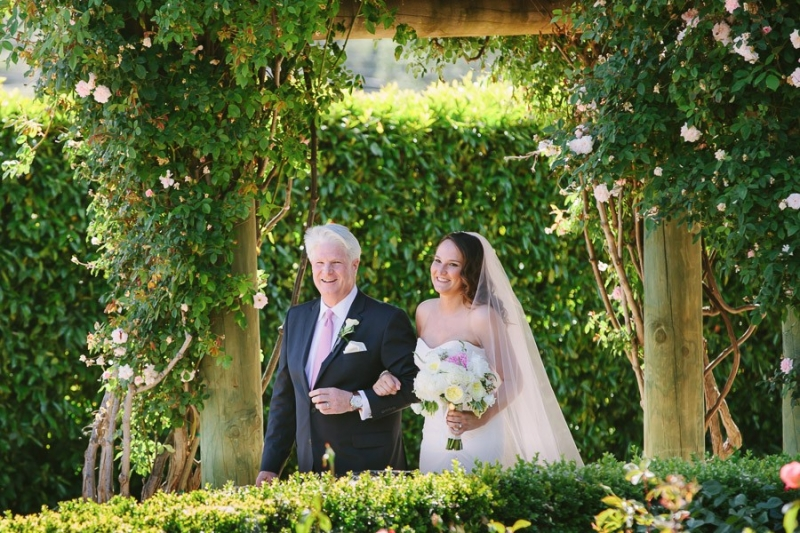 Bernardus Lodge Carmel Wedding. Bride walking with her father to her wedding ceremony. The walkway is covered by roses.