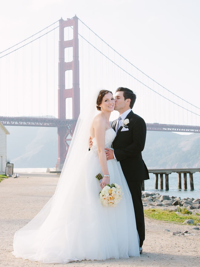 Best engagement photo locations in San Francisco. Bride and groom hugging in front of the Golden Gate Bridge.