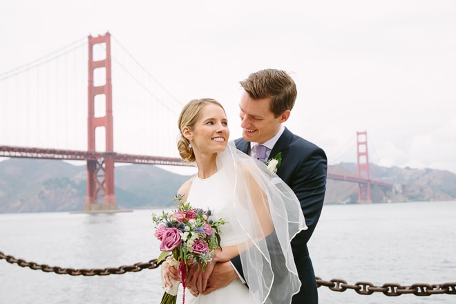 Best engagement photo locations in San Francisco. Bride and groom standing in front of the Golden Gate Bridge at Crissy Field