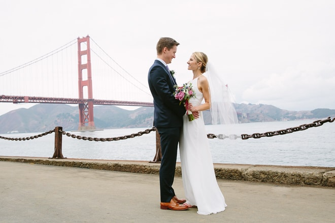 Best wedding photo location in San Francisco. Bride and groom standing in front of the Golden Gate Bridge at Crissy Field