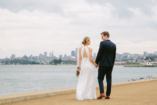 San Francisco wedding photography. Bride and groom at Crissy Field with a view of the San Francisco skyline behind them.