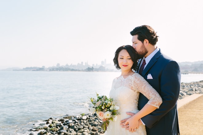 San Francisco wedding photographer. Groom kissing his bride with a view of the San Francisco skyline in the background