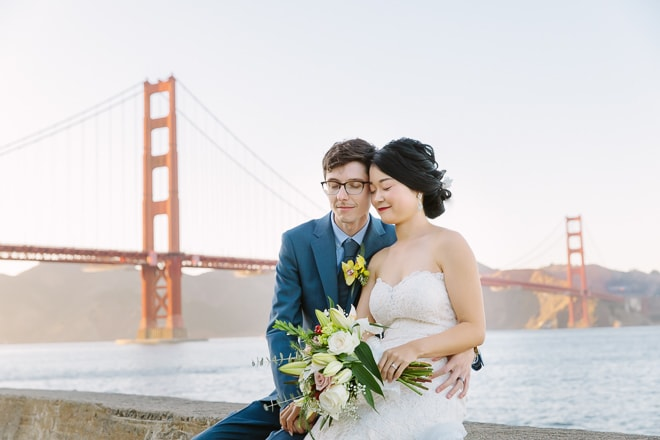 Crissy Field San Francisco wedding. Bride and groom sitting in front of the Golden Gate Bridge