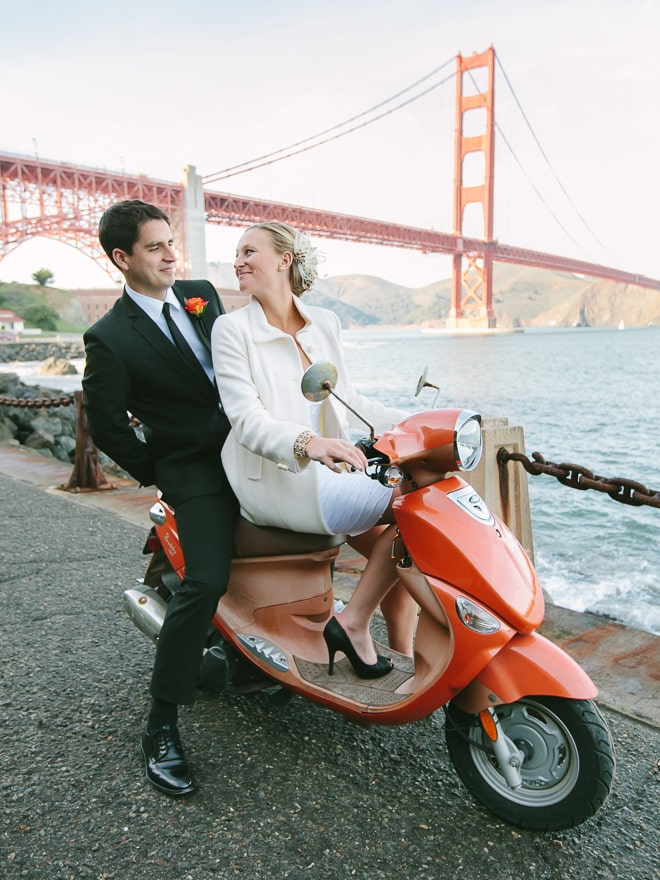 Bride and groom riding on an orange Vespa scooter in front of the Golden Gate Bridge at Fort Point and Crissy Field in San Francisco.