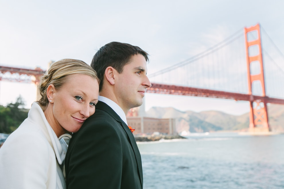 Bride and groom standing in front of the Golden Gate Bridge in San Francisco