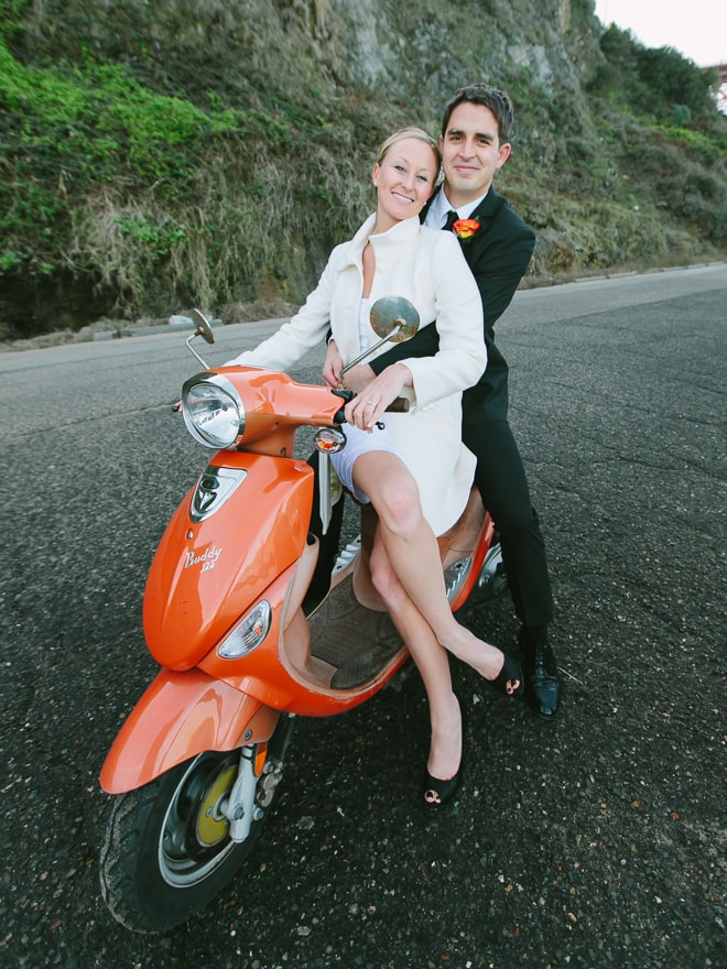 Bride and groom sitting together on an orange Vespa scooter. San Francisco wedding photographer, Lilia Photography