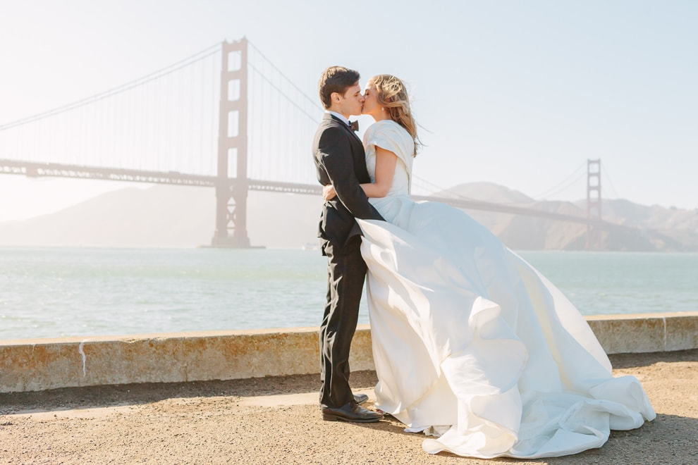 Bride and groom kissing on a pier in front of the Golden Gate Bridge. San Francisco wedding photographer, Lilia Photography