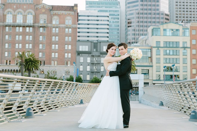 Best engagement photo locations in San Francisco. Bride and groom standing on Pier 14