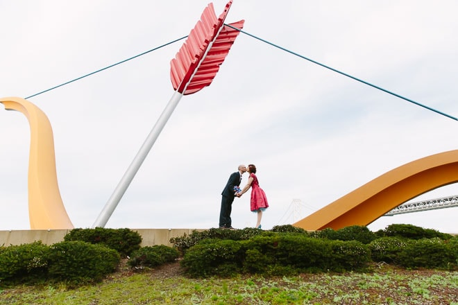 Best engagement photo locations in San Francisco. Bride and groom kiss in front of Cupids Span sculpture on the Embarcadero.