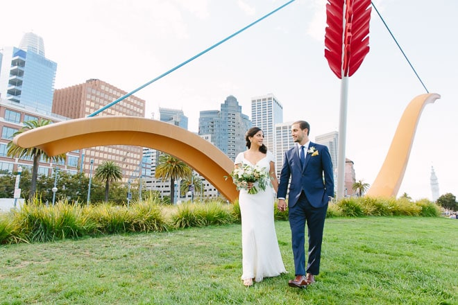 Best engagement photo locations in San Francisco. Bride and groom holding hands and walking in front of Cupids Span sculpture on the Embarcadero.