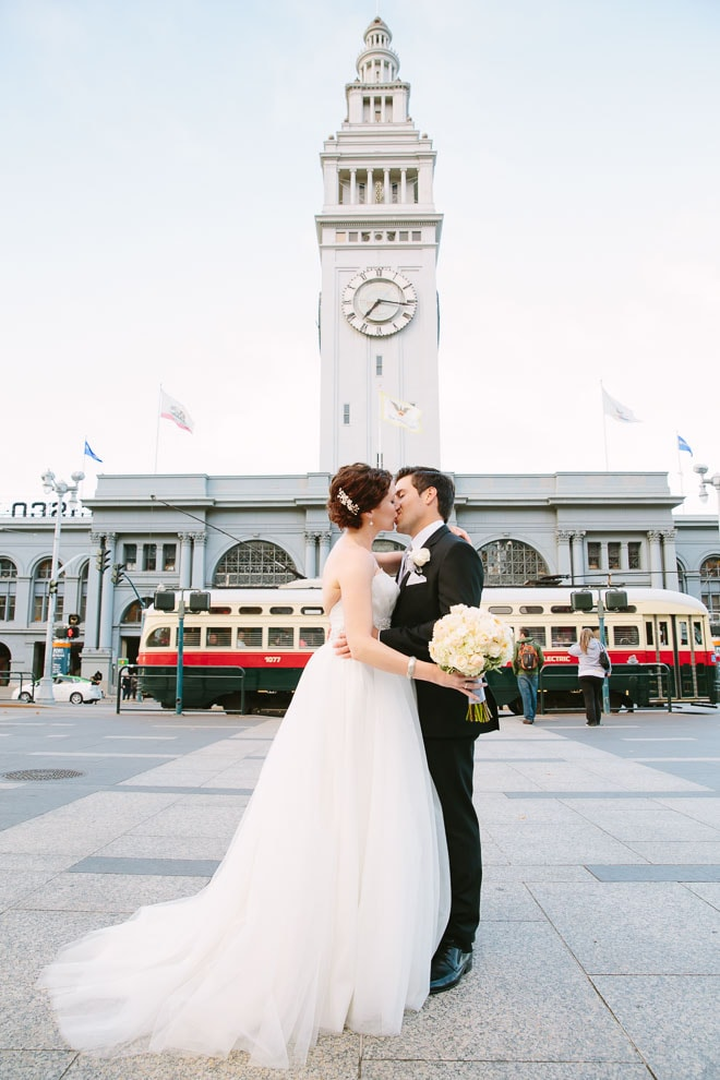 Bride and groom kiss in front of the Ferry Building in San Francisco