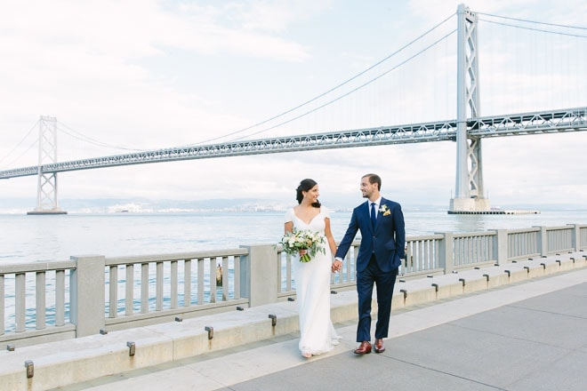 Bride and groom hold hands and walk together on the Embarcadero in San Francisco with a view of the Bay Bridge in the background
