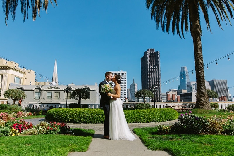 Bride and groom kiss on the rooftop of the Fairmont Hotel. San Francisco wedding venue.