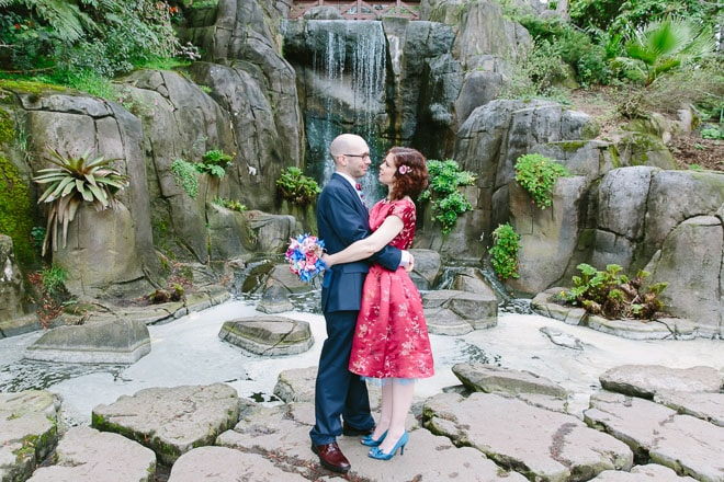 Golden Gate Park wedding. Bride and groom holding each other and standing in front of Huntington Falls.