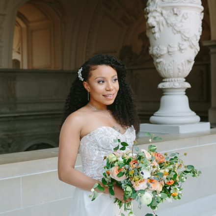 Bride holding a bridal bouquet while standing on the Fourth Floor at her San Francisco City Hall wedding