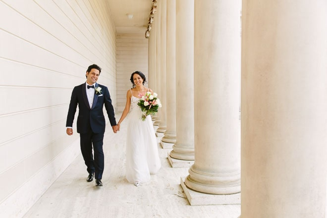 Legion of Honor Wedding. Bride and groom walking together surrounded by white columns