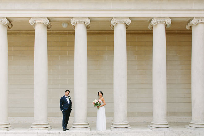 Legion of Honor wedding. Bride and groom standing between white columns.