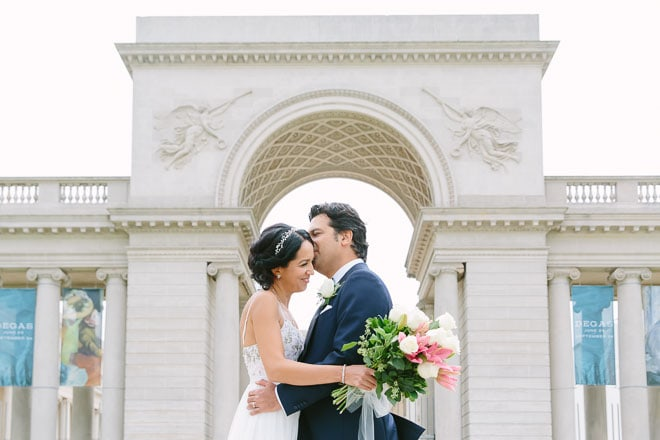 Legion of Honor Wedding. Groom kisses his bride on the cheek while standing in front of the gate of the Legion of Honor museum.