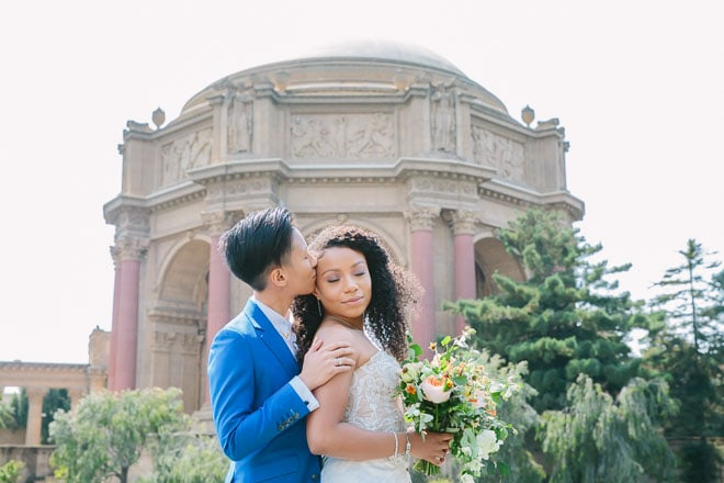 Palace of Fine Arts wedding. Bride kisses her new wife on the forehead while standing in front of the dome.