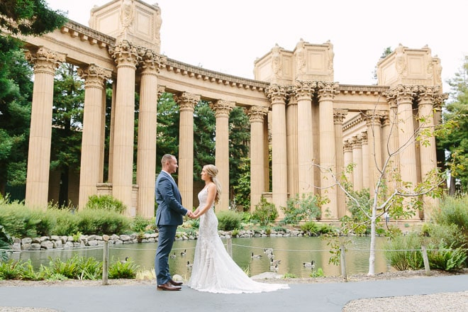 Palace of Fine Arts wedding. Bride and groom holding hands, standing in front of columns and a lagoon.