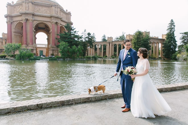Palace of Fine Arts wedding. Bride and groom walking with their dog.