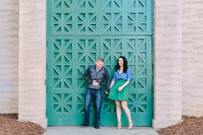 Palace of Fine Arts engagement session. Man and woman holding hands and laughing in front of large green doors.