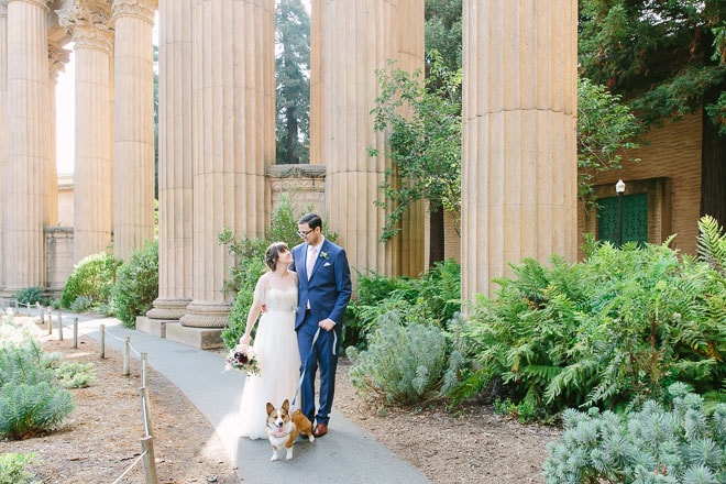 Palace of Fine Arts wedding. Bride and groom walking their dog surrounded by tall columns.