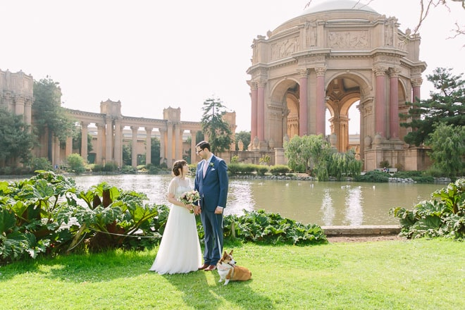 Palace of Fine Arts wedding. Bride and groom standing in front of the dome with their dog.