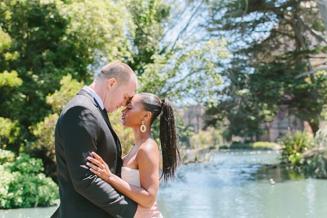 Palace of Fine Arts engagement session. Bride and groom hugging each other in front of trees and the lagoon.