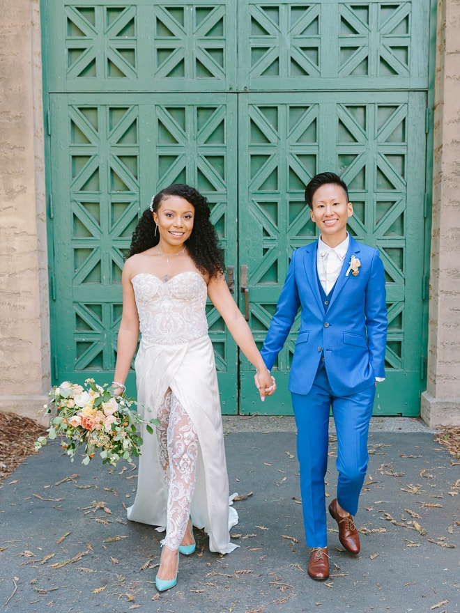 Couple holding hands and walking in front of green doors