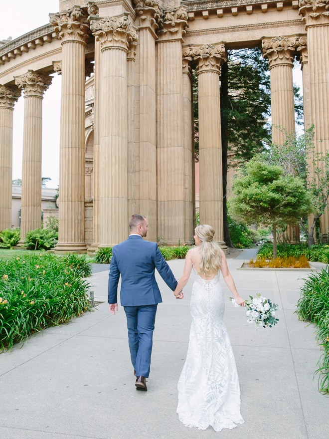 Couple holding hands and standing in front of the Palace of Fine Arts in San Francisco