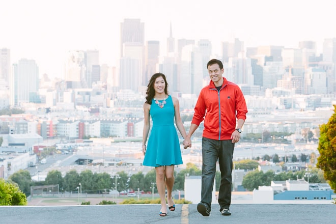 Best engagement session photo locations in San Francisco. Couple embracing with a view of the San Francisco skyline behind them.