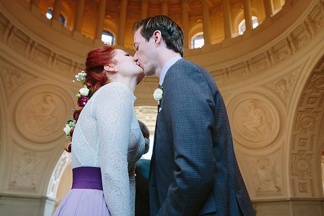 Bride and groom kiss during their wedding ceremony on the Fourth Floor North Gallery of San Francisco City Hall