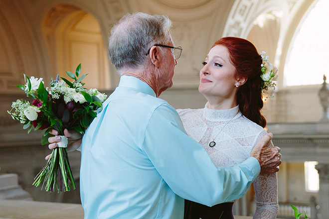Grandfather embracing his granddaughter after her wedding ceremony