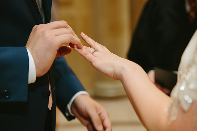 Close up of groom placing the ring on his bride's finger