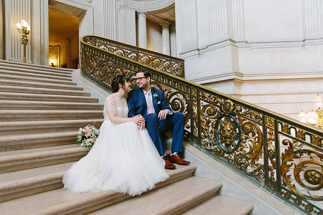 Bride and groom sitting on the stairs inside San Francisco City Hall