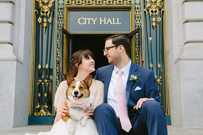 Bride and groom with their corgi dog at their wedding in front of San Francisco City Hall