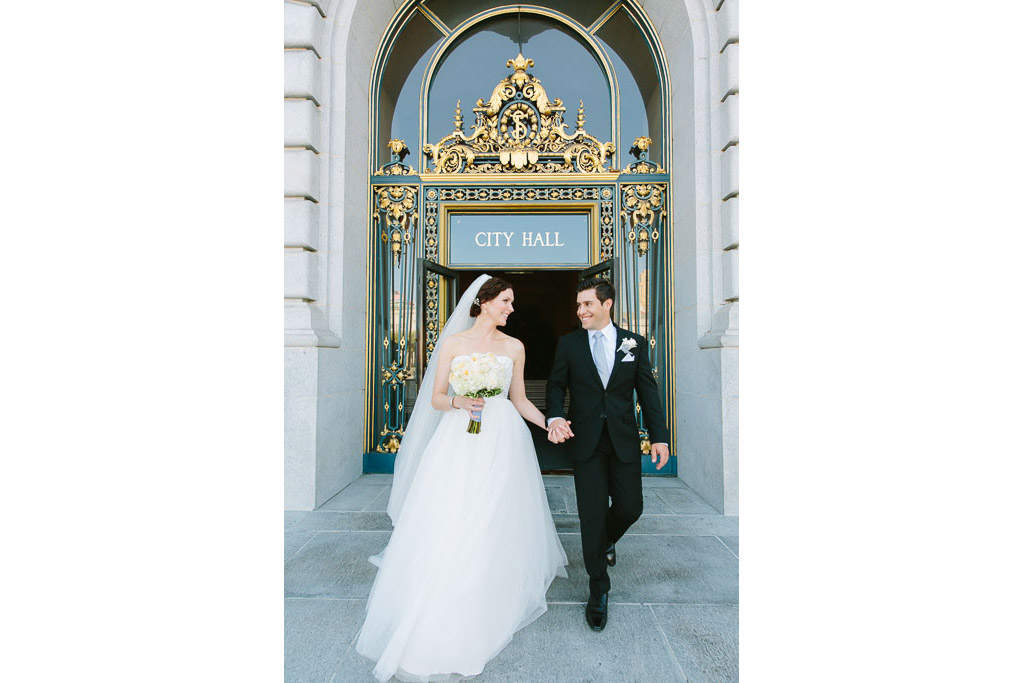 Bride and groom walking near the front entrance of San Francisco City Hall