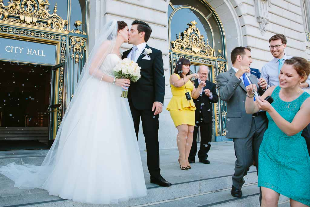 Wedding guests blowing bubbles on the steps of San Francisco City Hall