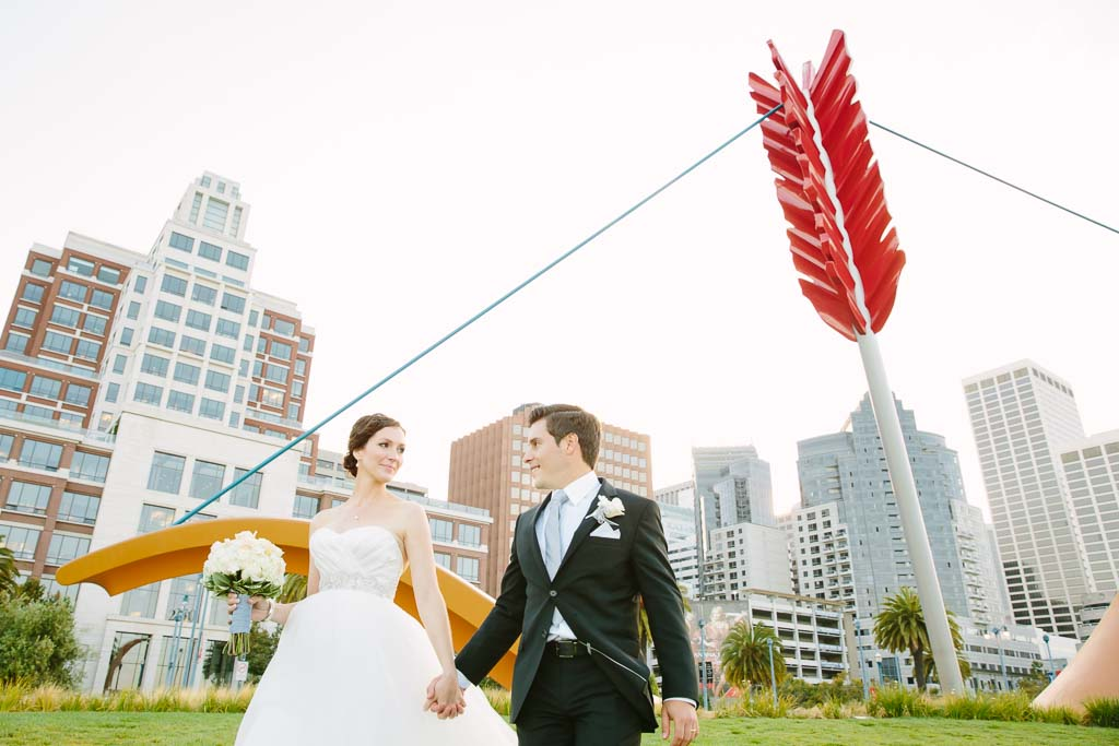 San Francisco wedding couple walking along the Embarcadero with Cupid's Span behind them