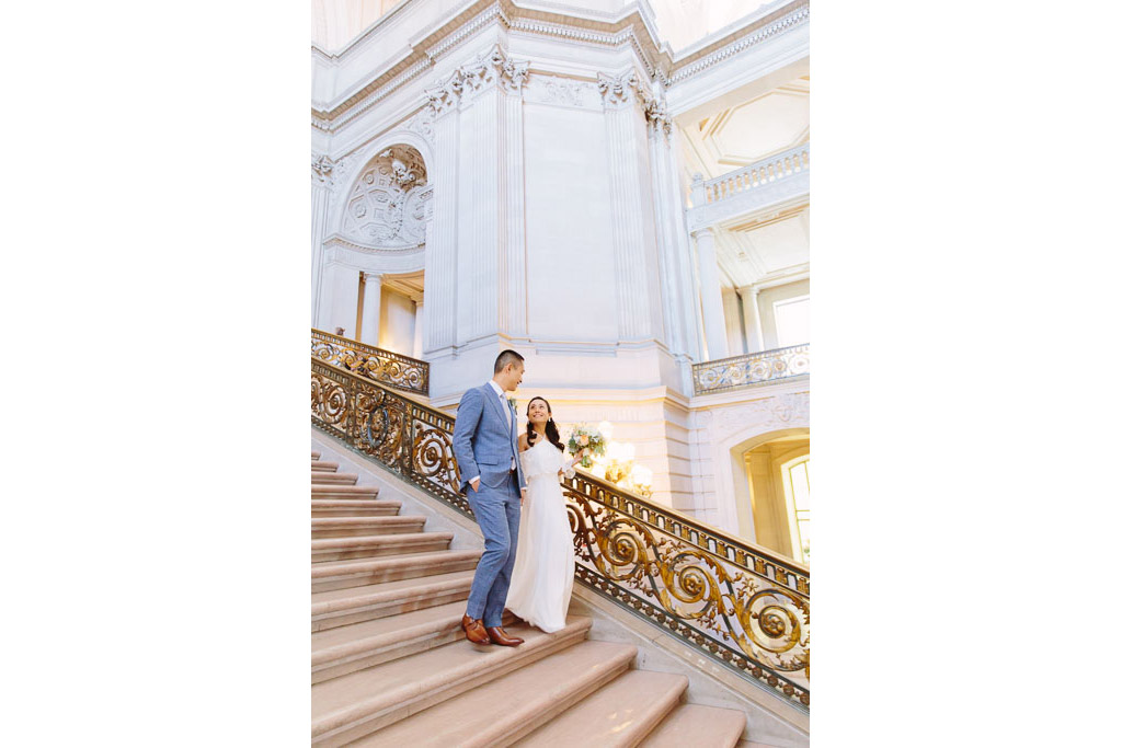 Bride and groom walking down the Grand Staircase inside San Francisco City Hall