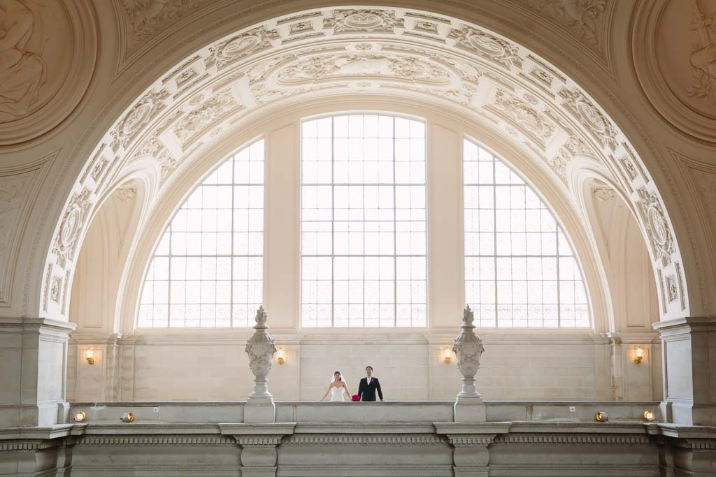 Bride and groom surrounded by the beautiful window of the Fourth Floor inside San Francisco City Hall
