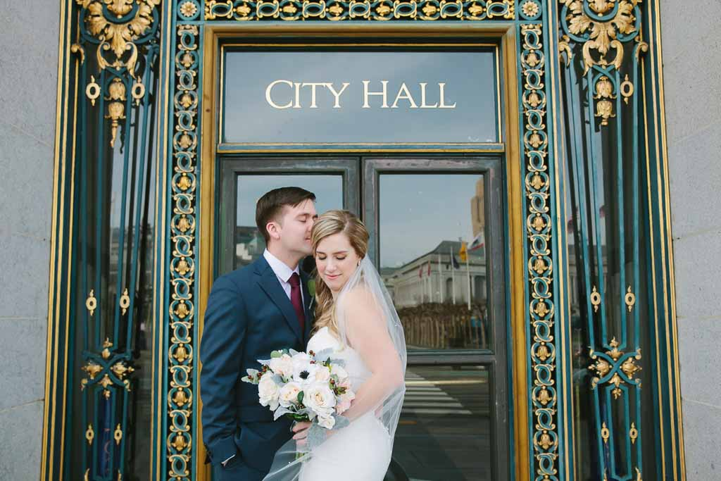 Romantic San Francisco City Hall wedding. Groom kissing the forehead of his bride