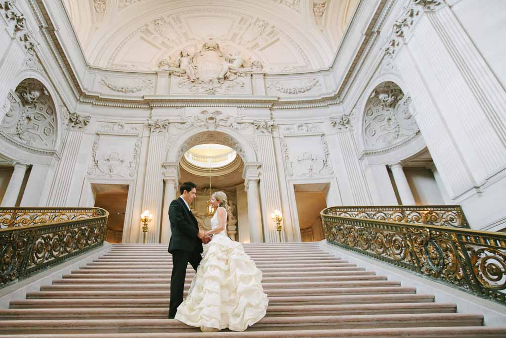 Bride and groom looking at each other and standing on the Grand Staircase inside San Francisco City Hall