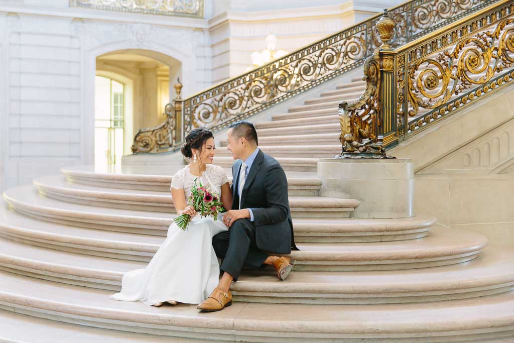 Bride and groom sitting together on the Grand Staircase inside San Francisco City Hall