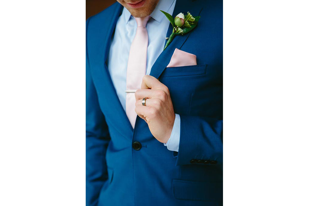 Close up of groom suit and wedding ring