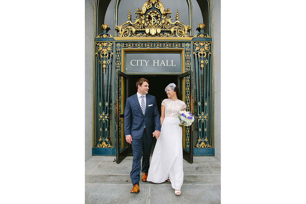 Bride and groom walking out the front door of SF City Hall